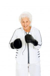 Idősebb hölgy box-kesztyűkkel a kezén