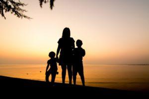 Csonka család áll a tengerparton a naplementében