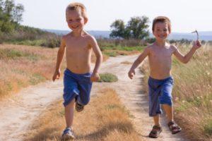 Kisfiúk szaladnak a földúton