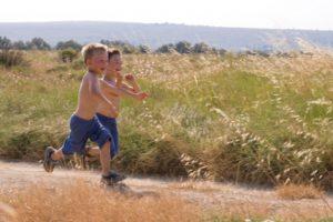 Kisfiúk szaladnak a mezőn